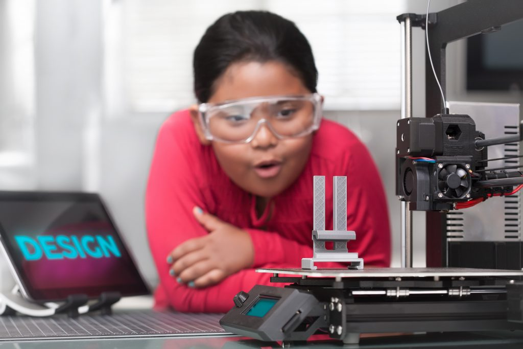 Young girl in awe of a 3d printer in progress